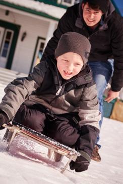 boy sliding down snowy hill on a toboggan