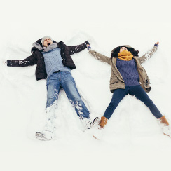 young man and woman making snow angels in the snow