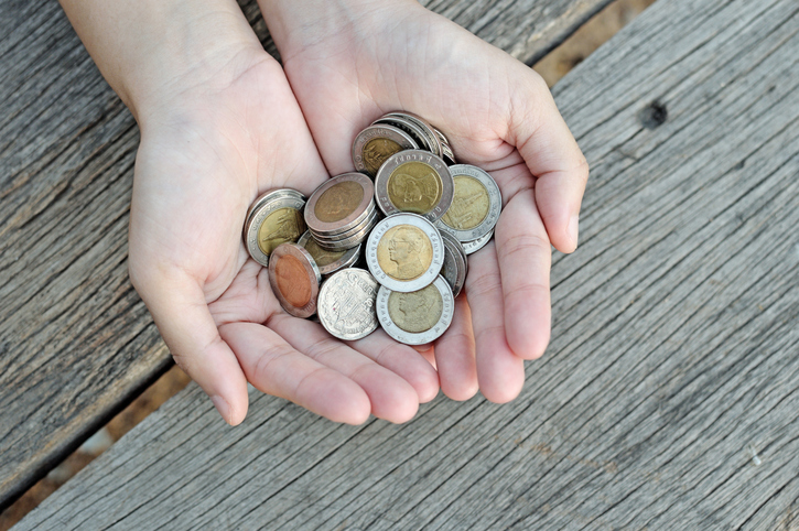 Women hold  coins on wood table