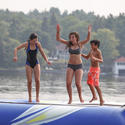 Picture of three kids bouncing on a water trampoline