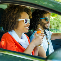 young man and woman with sunglasses driving car
