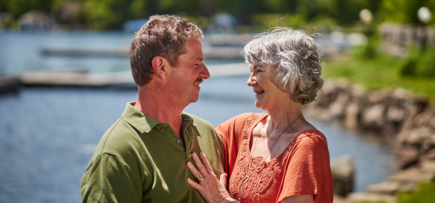 photo of an elderly man and woman smiling and embracing outdoors