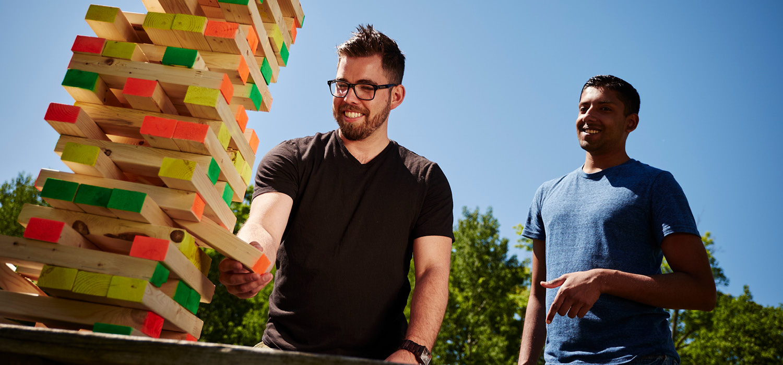 two smiling men play jenga outdoors