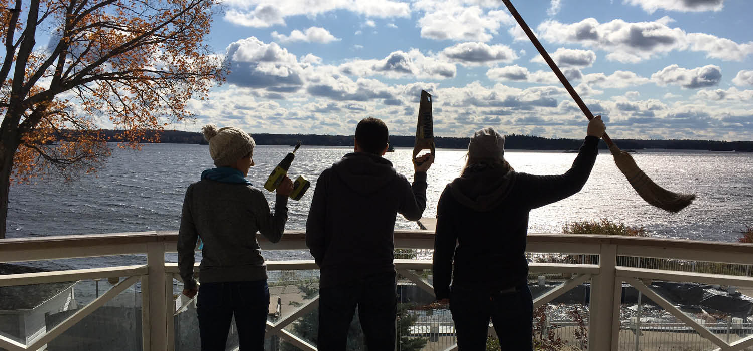 Photo of a three workers holding tools in the air, with lake in background