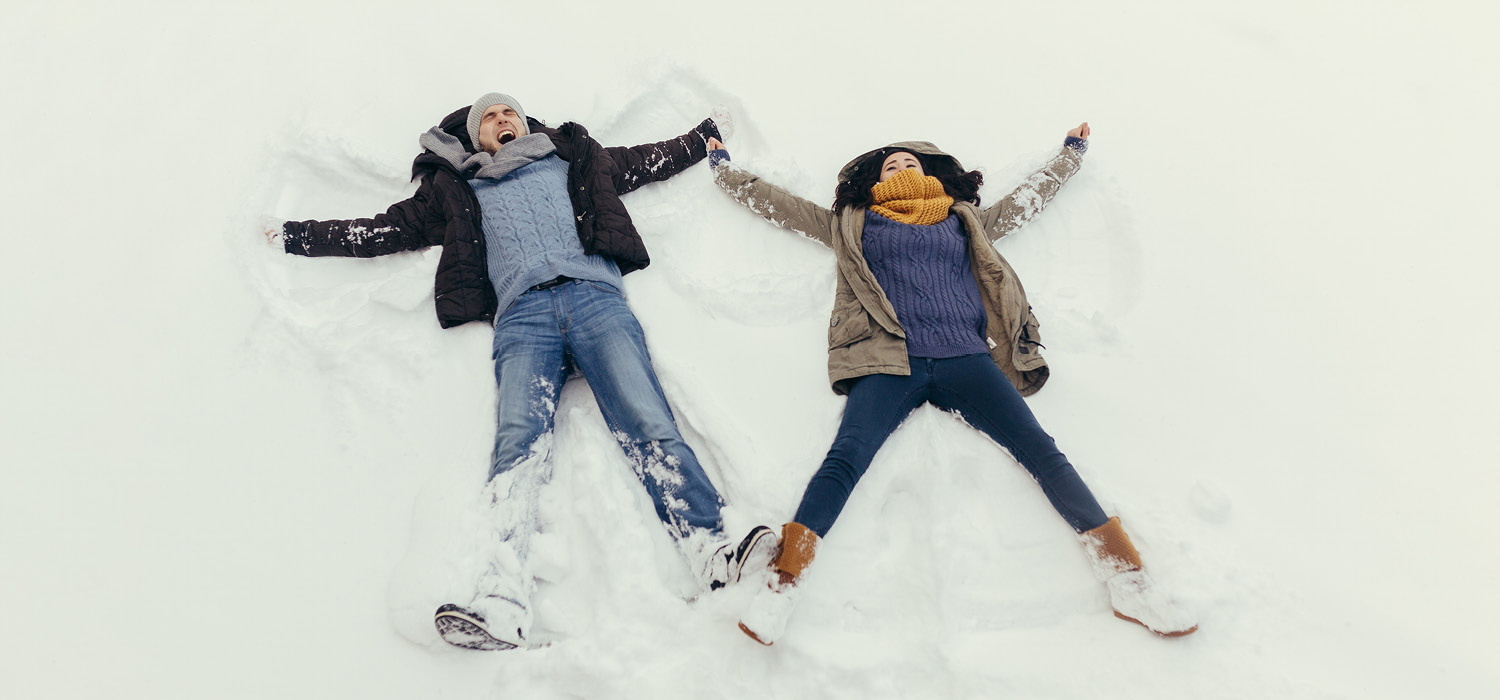 A young woman and man lay on the snowy ground, making snow angels.