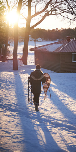 a woman, holding snowshoes and a sled, walking towards a cottage in winter