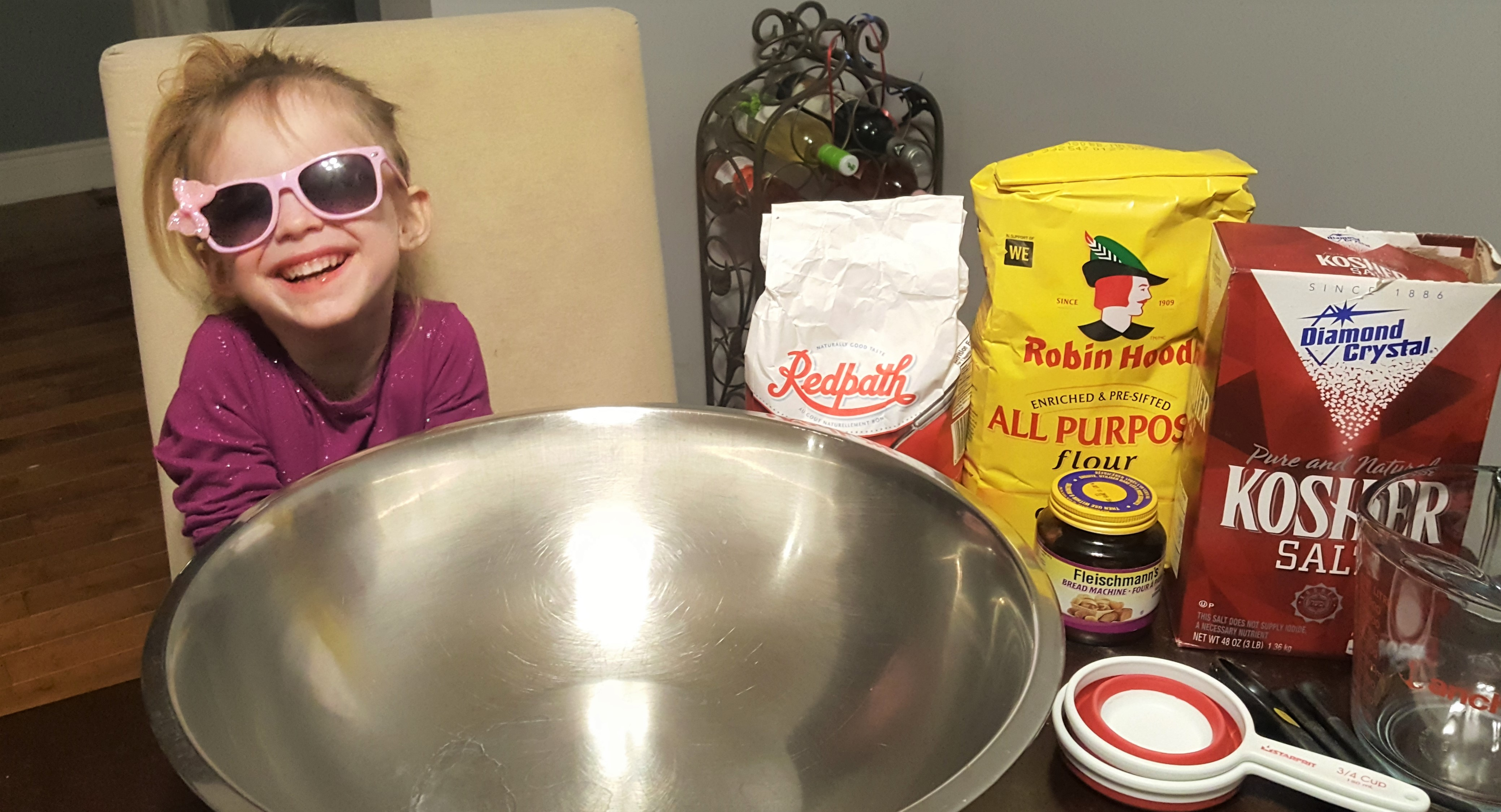 Young child wearing sunglasses and laughing with a mixing bowl and baking ingredients on a table in front of her.