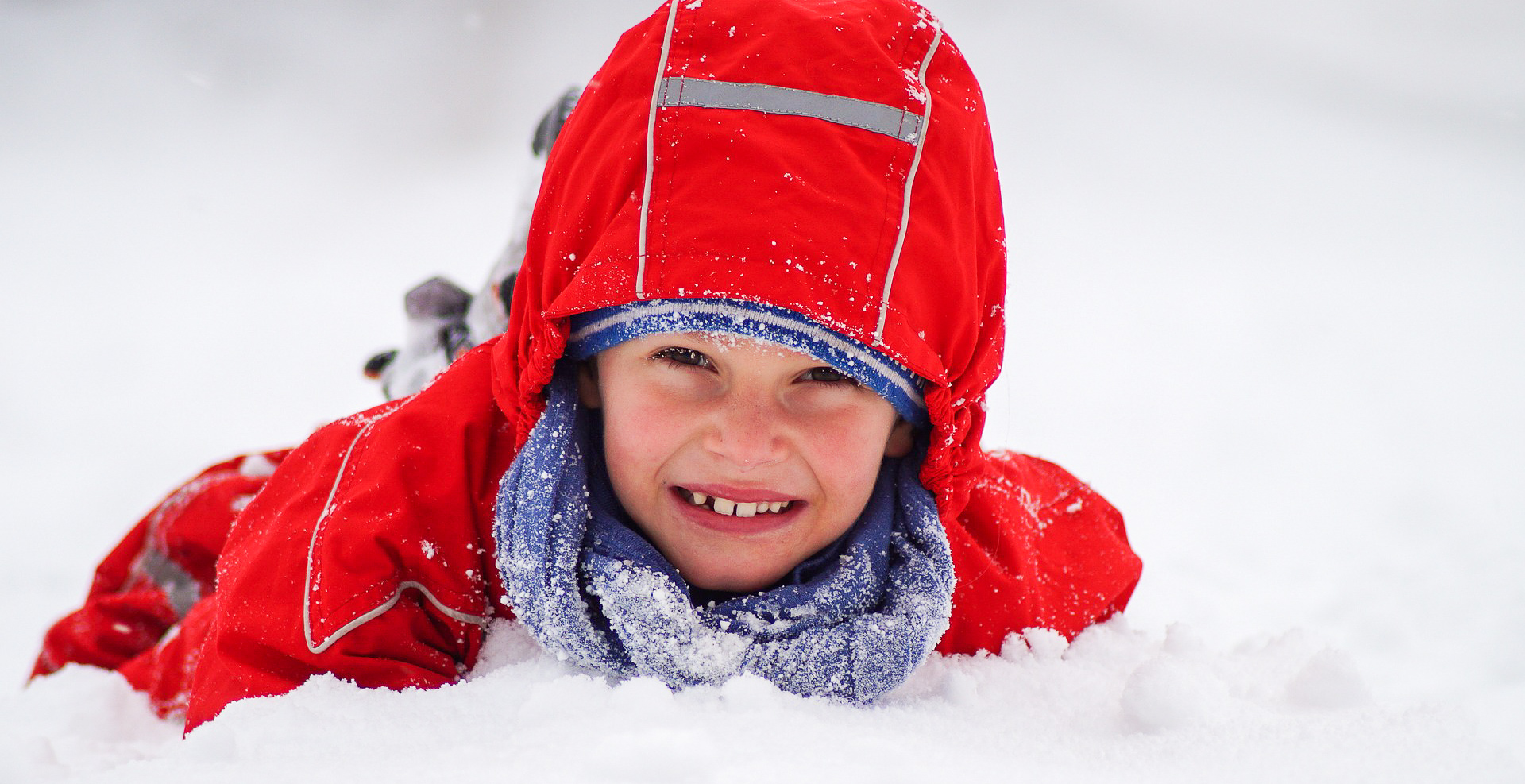 Photo of a young child in a red snowsuit playing in the snow, facing the camera and smiling